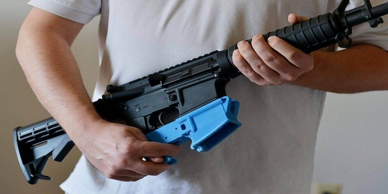 """An AR15 rifle with a bright blue 3D printed """"lower"""" reciever."""